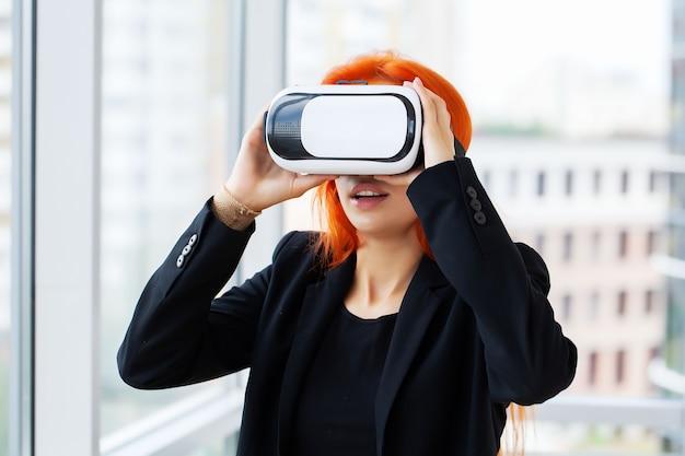 Femme dans un casque de réalité virtuelle pointant dans l'air alors qu'il était sur son lieu de travail au bureau.