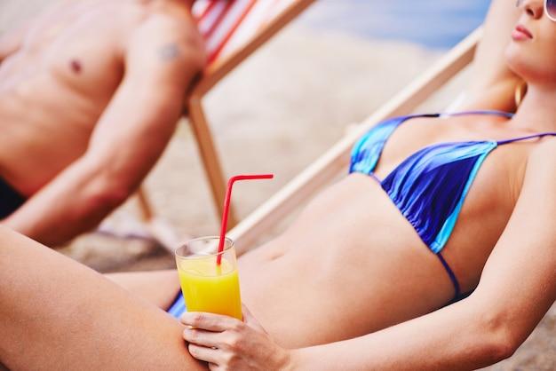 Femme dans une chaise longue avec une boisson
