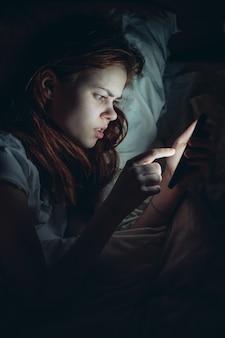 Femme dans la chambre à coucher avec un téléphone dans ses mains se trouve dans le lit communiquant