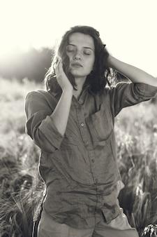 Femme dans un champ d'été. brunette dans une chemise verte.