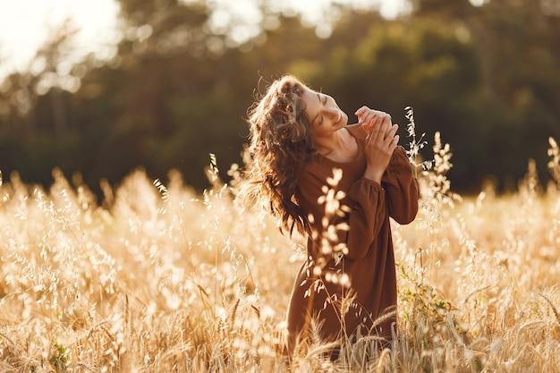 Femme dans un champ d'été. brunette dans un pull marron.