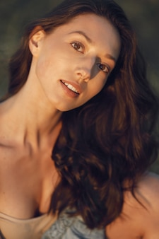 Femme dans un champ d'été. brunette dans un sous-vêtement marron.