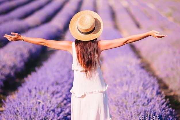Femme dans le champ de fleurs de lavande au coucher du soleil en robe blanche et chapeau