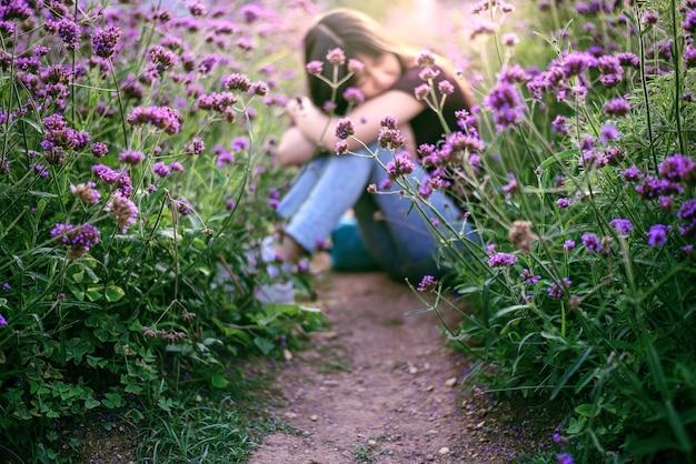 Femme dans le champ de fleurs de verveine le soir dans la douce lumière du soleil