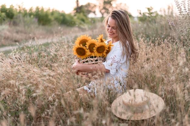 Femme, dans, champ, tenue, bouquet tournesol