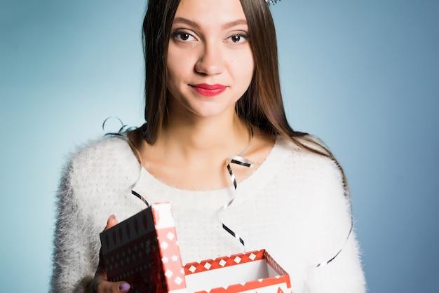 La femme dans un chapeau de fête tient une boîte-cadeau dans des mains
