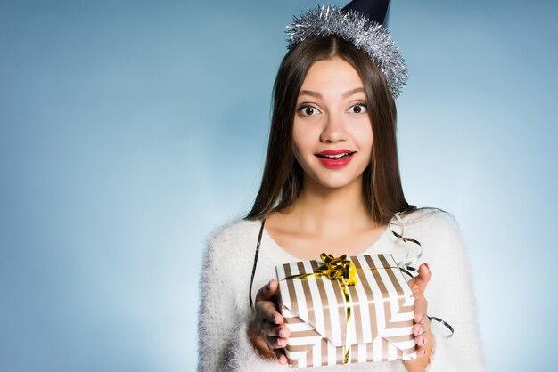 La femme dans un chapeau de fête tient une boîte-cadeau dans ses mains