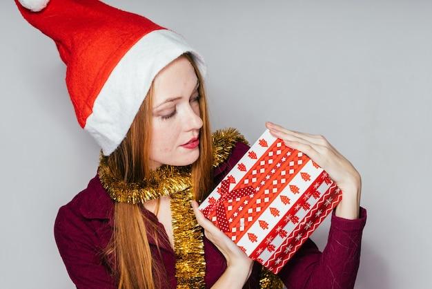 La femme dans un chapeau de noël tient un cadeau dans ses mains