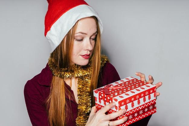 La femme dans un chapeau de nouvelle année tient un cadeau dans ses mains