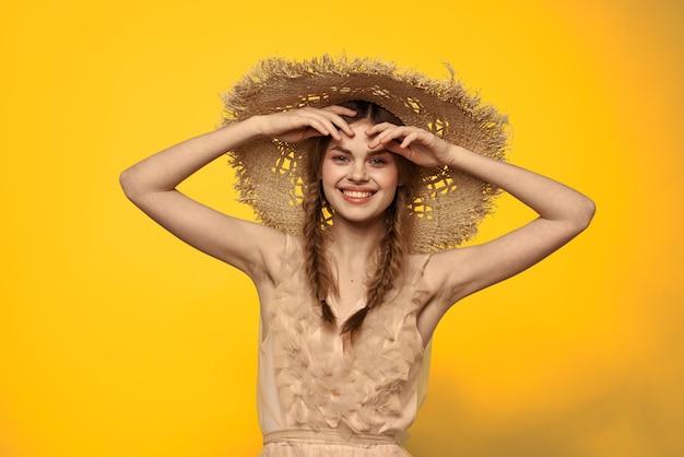 Femme dans un chapeau de paille dans ses mains sur une émotions jaune