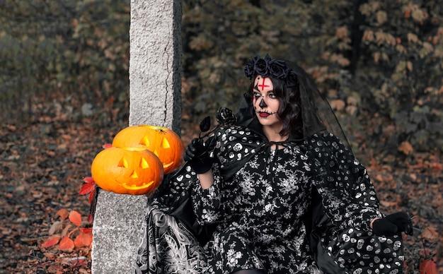Une femme dans un chapeau de sorcière avec une tête de citrouille effrayante jack lanterne et une forêt brumeuse pour halloween