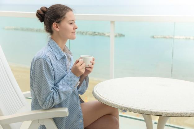 Femme, dans, chemise homme, boire café, dans, maison, terrasse