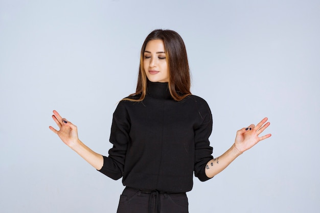 Femme dans une chemise noire montrant un signe de plaisir.