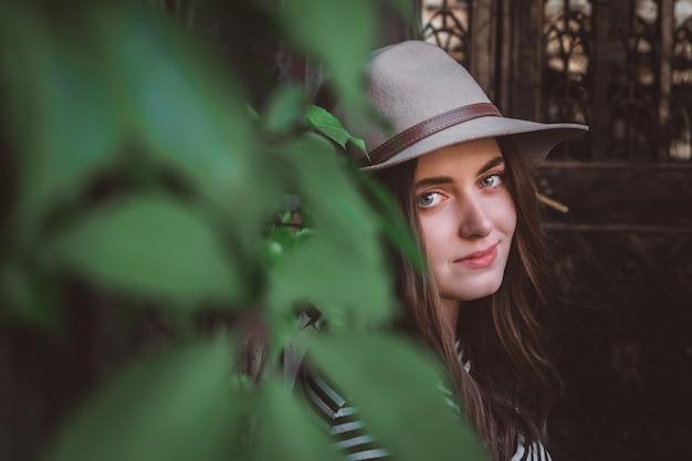 Femme dans une chemise rayée tenant son chapeau se dresse sur le fond de la vieille maison et des feuilles vertes