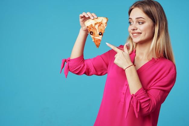 Femme dans une chemise rose avec une pizza dans ses mains gros plan de malbouffe. photo de haute qualité
