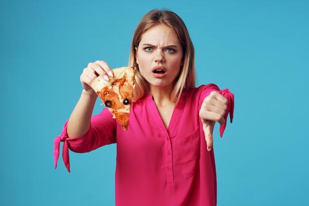 Femme dans une chemise rose avec pizza dans ses mains gros plan de la malbouffe