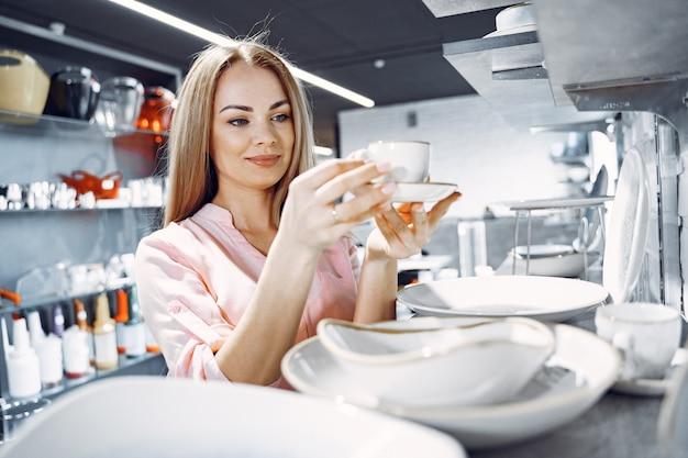 Femme dans un chemisier rose achète des plats dans le magasin