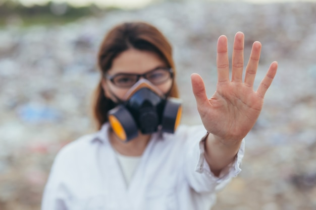 Une femme dans une combinaison respiratoire protégée dans les décharges, se tenant la main devant, essayant d'arrêter la pollution de la planète, montre un panneau d'arrêt avec ses mains