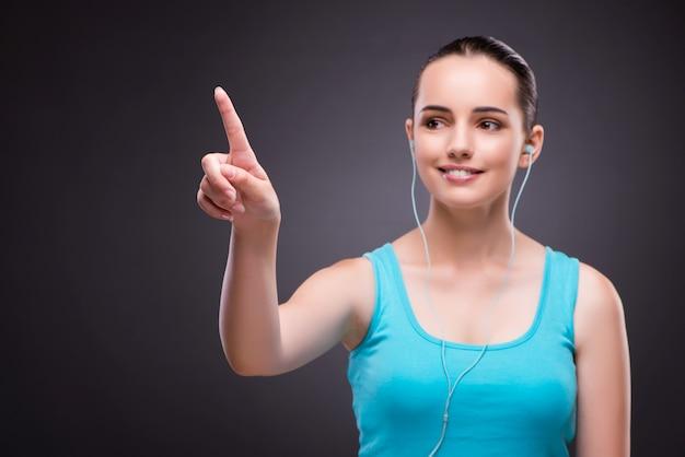 Femme dans le concept sportif en appuyant sur les boutons