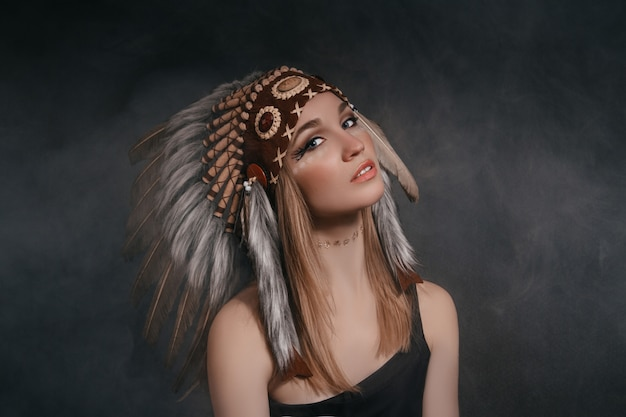 Femme dans le costume d'indiens d'amérique sur fond gris
