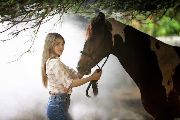 Femme dans un costume de style cow-girl se trouve dans un ranch de chevaux avec un environnement de ferme de l'ouest.