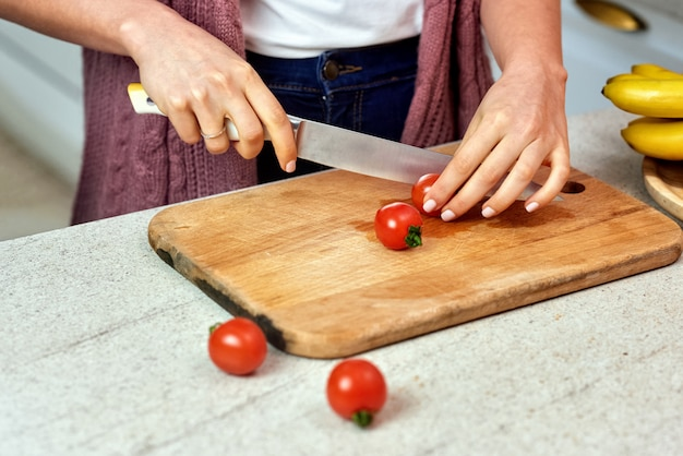 Une femme dans la cuisine coupe des tomates pour la salade