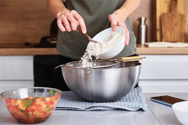 Femme dans la cuisine cuire une pâte. les mains versent la farine dans un bol