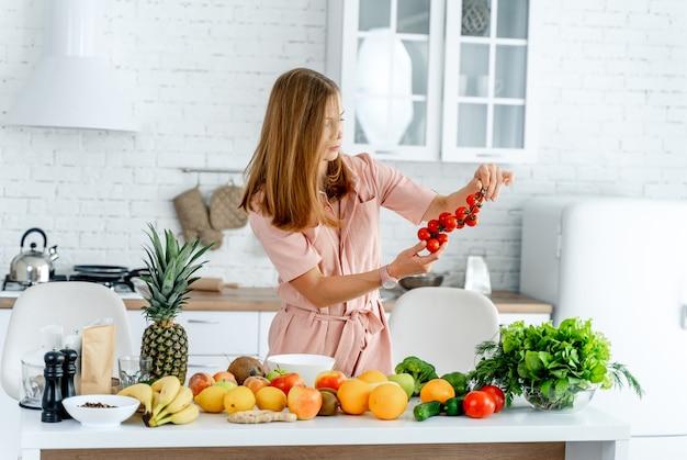 Femme dans la cuisine prête à préparer un repas avec des légumes et des fruits.