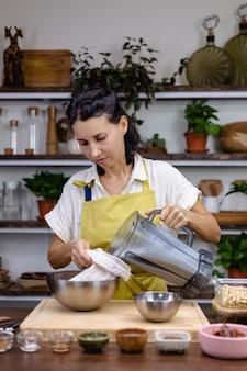 Femme dans la cuisine avec processus de fabrication de pudding de chia