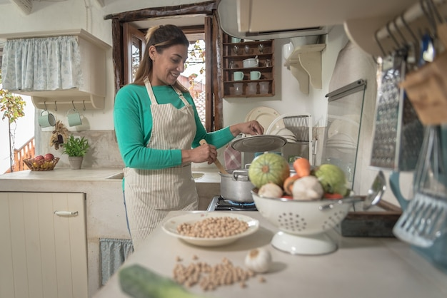 Femme dans une cuisine vintage traditionnelle faisant un repas avec de vieux pots et légumes