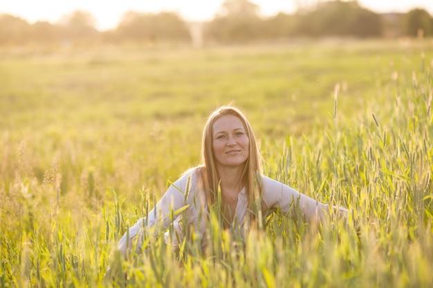 La femme dans le domaine apprécie l'harmonie de blé avec la nature