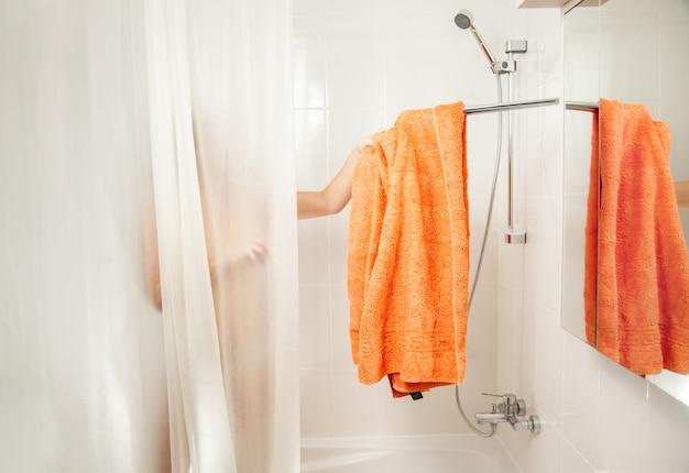 Femme dans la douche enlevant la serviette orange du crochet