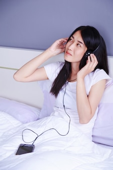 Femme dans les écouteurs, écouter de la musique depuis le smartphone sur le lit dans la chambre