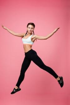 Femme, dans, élégant, tenue sport, jumpig, à, large, écarté, mains
