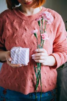 Femme dans une fille de pull en laine corail tenant une boîte cadeau avec ruban et feuilles vertes fraîches et fleurs roses épanouies
