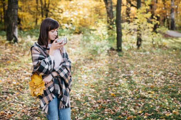 Femme dans la forêt d'automne, boire du thé avec des feuilles dans ses mains sun