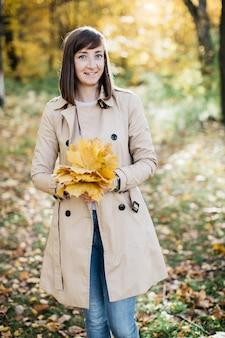Femme dans la forêt d'automne avec des feuilles dans ses mains la femme est heureuse