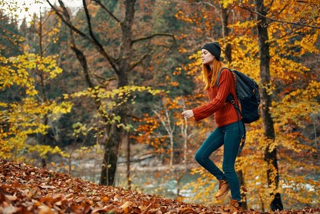 Femme dans la forêt d'automne près du paysage fluvial feuilles jaunes tourisme