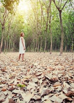 Femme dans la forêt avec le sol couvert de feuilles