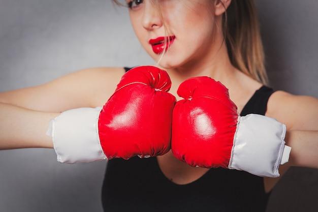Femme dans des gants de boxe sur fond gris