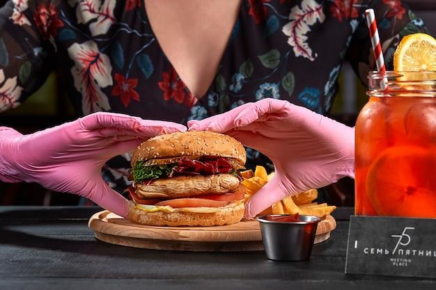 Femme dans des gants en caoutchouc rose prenant un hamburger avec un steak de porc
