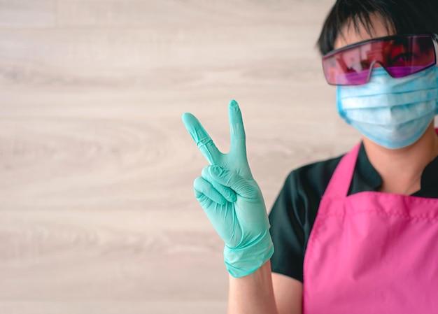 Femme dans des gants en latex et un tablier rose tenant les mains comme un symbole de victoire ok, j'espère gagner medical