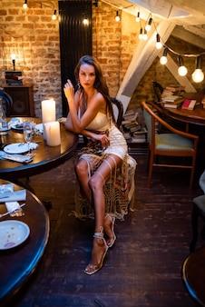 Femme dans un intérieur de soirée confortable avec des bougies