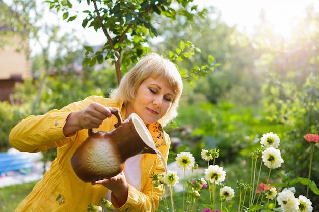 Une femme dans le jardin arrosant des fleurs et des plantes