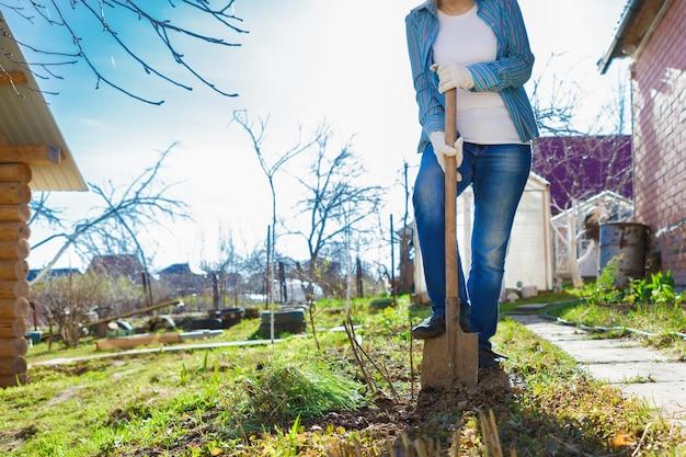Une femme dans le jardin au printemps avec des fleurs. elle plante des semis. une femme d'âge moyen creuse un lit de jardin avec une pelle.