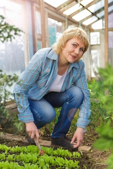 Une femme dans le jardin au printemps avec des fleurs. elle plante des semis. une femme d'âge moyen dans une serre avec un râteau.