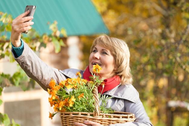Une femme dans le jardin d'automne récolte et enlève les ordures