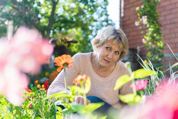 Une femme dans le jardin choisit des fleurs pour les semis. une femme d'âge moyen a l'air surprise. elle travaille au village.