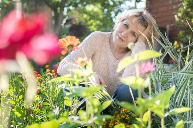 Une femme dans le jardin choisit des fleurs pour les semis. une femme d'âge moyen prend soin des plantes. elle travaille au village.