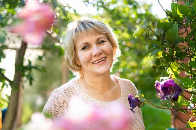 Une femme dans le jardin choisit des fleurs pour les semis. une femme d'âge moyen regarde dans l'objectif de la caméra. elle travaille au village.